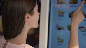 Beautiful attractive woman in mall. Ordering food via self-service machine at fast-food chain restaurant