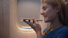 Beautiful attractive woman near airplane window. Long distance flight. Talking on her smartphone stock video footage