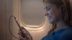 Beautiful attractive woman near airplane window. Long distance flight. Talking to friend via Skype. Beautiful attractive young woman sitting near airplane window stock video footage