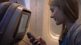 Beautiful attractive woman near airplane window. Long distance flight. Using on-board TV screen stock footage