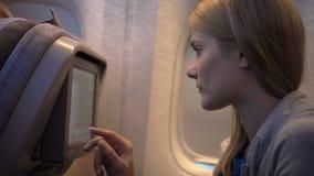 Beautiful attractive woman near airplane window. Long distance flight. Using on-board TV screen stock video