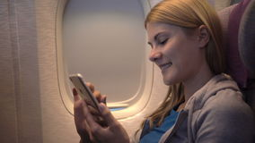 Beautiful attractive woman near airplane window. Long distance flight. Using smartphone, browsing. Beautiful attractive young woman sitting near airplane window stock footage