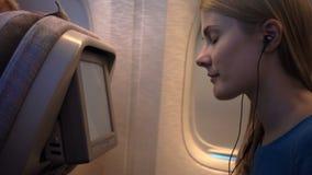 Beautiful attractive woman near airplane window. Long distance flight. Watching on-board TV screen stock video footage