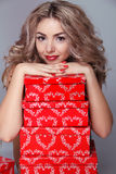 Beautiful attractive woman with red gift box on gray background Royalty Free Stock Photography