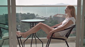 Beautiful attractive woman sitting on balcony chair relaxing enjoying the view. Turquoise sea trees. Beautiful attractive young woman sitting on terrace chair stock video