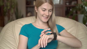 Beautiful attractive woman sitting in chair at home using her black smartwatch, browsing, reading stock video footage