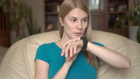 Beautiful attractive woman sitting in chair at home using her black smartwatch, dictating message stock footage