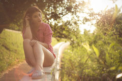 Beautiful and attractive woman sitting on a side, wearing casual denim shorts Stock Photos