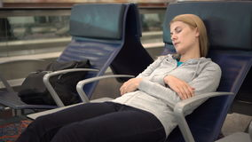 Beautiful attractive woman sleeping in airport terminal. Long distance connected flights jet-lag. Beautiful attractive young woman sleeping in chair in airport stock video