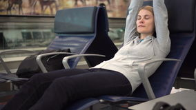 Beautiful attractive woman sleeping in airport terminal. Long distance connected flights jet-lag. Beautiful attractive young woman sleeping in chair in airport stock footage