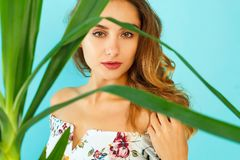 Beautiful attractive woman standing near green plant over blue b Royalty Free Stock Photography