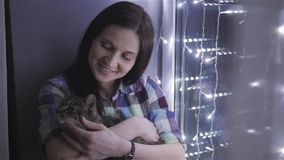Beautiful Attractive Woman Stroking a Cat Sitting On Windowsill Decorated With Garlands stock video