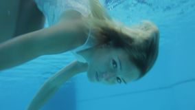 Beautiful attractive woman in swimsuit posing, swimming, spinning underwater stock video footage