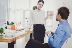 Beautiful attractive woman talking to her colleague stock photography