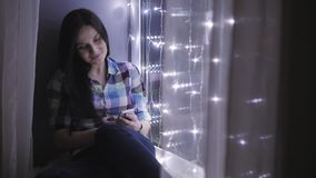Beautiful Attractive Woman Using Smartphone And Sitting On Windowsill Decorated With Garlands stock video footage