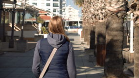 Beautiful attractive woman walking down the street, sun is shining. From behind. Off season resort. stock video