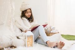 Woman relax in house during Christmas holiday. Beautiful attractive woman with white fur hat and sweater read book in bedroom at winter with copy space for text Stock Image