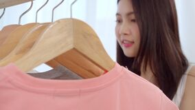 Beautiful attractive young Asian woman choosing her fashion outfit clothes in closet at home or store. Girl think what to wear