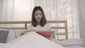 Beautiful attractive young Asian woman reading a book while lying on the bed when relax in her bedroom at home in the morning. Lifestyle women using relax time stock video footage