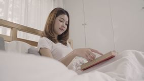 Beautiful attractive young Asian woman reading a book while lying on the bed when relax in her bedroom at home in the morning. Lifestyle women using relax time stock footage