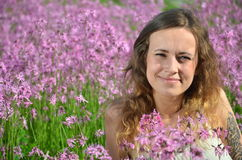 Beautiful attractive young girl on gorgeous meadow full of wild flowers Stock Photos