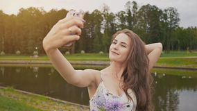 Beautiful attractive young girl with long hair and in dress is doing photo shoot using smartphone in city park. Beautiful attractive young girl with long hair stock footage