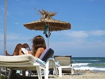 Beautiful Attractive Young Girl with Long Hair Sitting Relaxing and Reading Book under Straw Beach Parasol Umbrella and Blue Sky stock photo