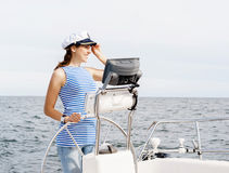Beautiful, attractive young girl pilots a boat Mediterranean Sea Royalty Free Stock Photography