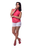 Beautiful, attractive young woman in blouse and short shorts thought, putting a finger to face, full length Royalty Free Stock Photo