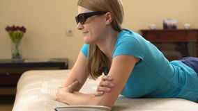 Beautiful attractive young woman in blue t-shirt lying on sofa and watching TV in 3D-glasses. stock footage