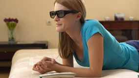 Beautiful attractive young woman in blue t-shirt lying on sofa and watching TV in 3D-glasses. stock video footage