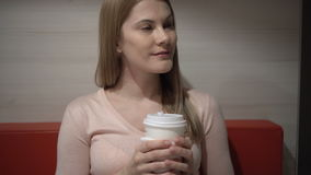 Beautiful attractive young woman drinking coffee in a cafe. Evening night. Paper coffee cup red sofa stock video