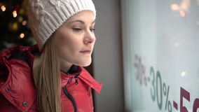 Beautiful attractive young woman looking at shop window. Red winter coat. Sales signs. Evening night. stock video
