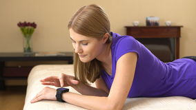 Beautiful attractive young woman lying on sofa and using her smartwatch. Beautiful attractive young woman lying on couch and using her smartwatch. 00366 stock video footage