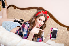 Beautiful attractive young woman pinup girl relaxing lying in bed with finger showing or pointing at mobile phone happy smiling stock photos