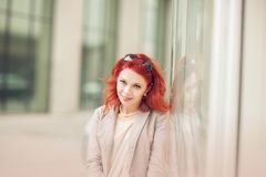 Beautiful, attractive young woman with red hair relaxing in town, shopping. Walking, summerly urban mood royalty free stock images