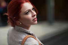 Beautiful, attractive young woman with red hair relaxing in town, shopping Stock Image