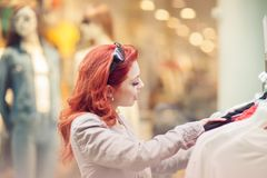 Beautiful, attractive young woman with red hair relaxing in town, shopping, looking at store offers. Walking, summerly urban mood Royalty Free Stock Image