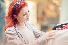 Beautiful, attractive young woman with red hair relaxing in town, shopping, looking at store offers. Walking, summerly urban mood Stock Photos