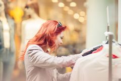 Beautiful, attractive young woman with red hair relaxing in town, shopping, looking at store offers. Walking, summerly urban mood Stock Photography