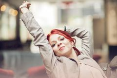 Beautiful, attractive young woman with red hair relaxing in town, shopping. Walking, summerly urban mood Royalty Free Stock Photo