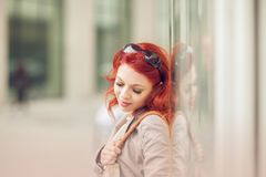 Beautiful, attractive young woman with red hair relaxing in town, shopping. Walking, summerly urban mood Stock Image