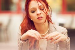 Beautiful, attractive young woman with red hair relaxing in town, street cafe. Summerly urban mood Stock Images