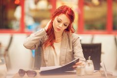 Beautiful, attractive young woman with red hair relaxing in town, street cafe royalty free stock photography