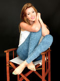 Beautiful Attractive Young Woman Sitting in Chair. A DSLR royalty free image, of attractive young woman sitting in directors chair relaxing with feet up snuggled Royalty Free Stock Photography