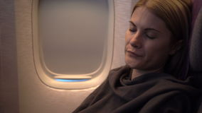 Beautiful attractive young woman sleeping near airplane window. Long distance flight night. Beautiful attractive young woman sleeping covered with plaid near stock video