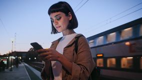 Activity in train. Beautiful and attractive young woman stands on station platform in night time, uses smartphone, to browse internet or scroll through news feed stock video