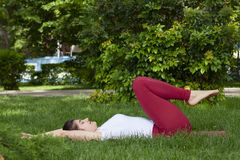 Beautiful attractive young woman stretching exercising in the park stock photography