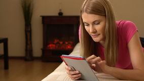 Beautiful attractive young woman tablet computer lying on sofa. Browsing Internet and smiling. 00333 stock footage