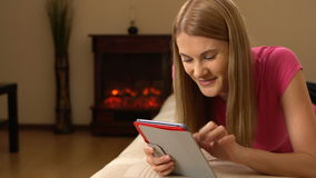 Beautiful attractive young woman tablet computer lying on sofa. Browsing Internet and smiling. stock video